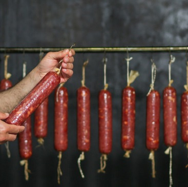 massive-sausage-producted-hanged-inside-factory_114579-2830