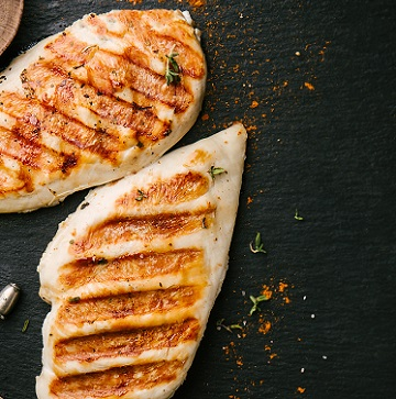 Tasty appetizing grilled baked chicken breast served on black slate background. View from above with copy space